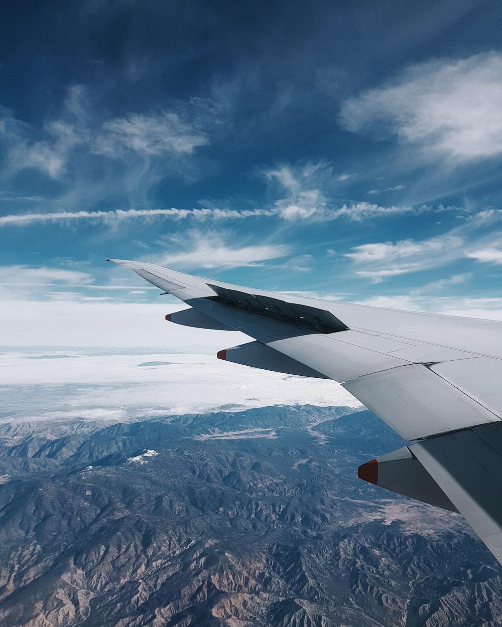 plane flying over grey hills