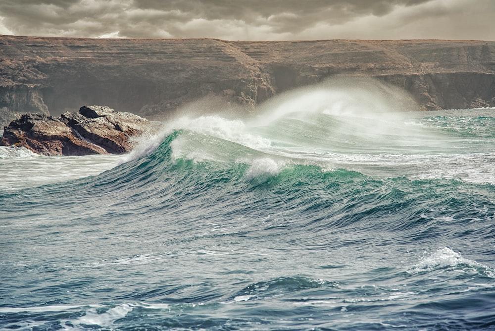 waves crashing through stones