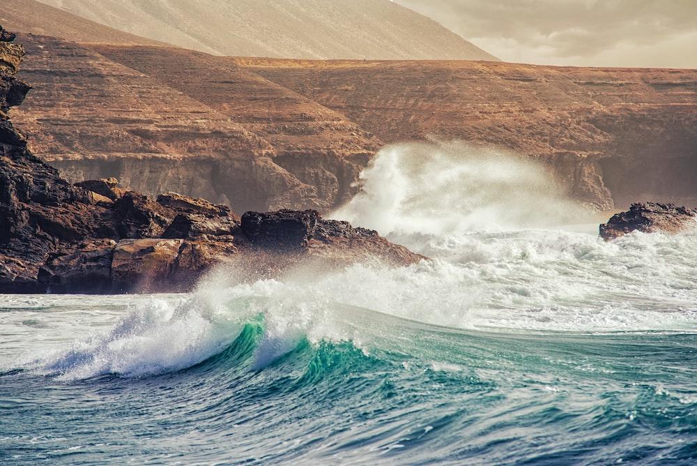 big waves crashing coastal rock during daytime