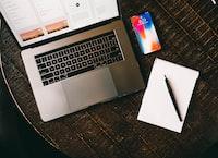 MacBook beside iPhone X on brown table