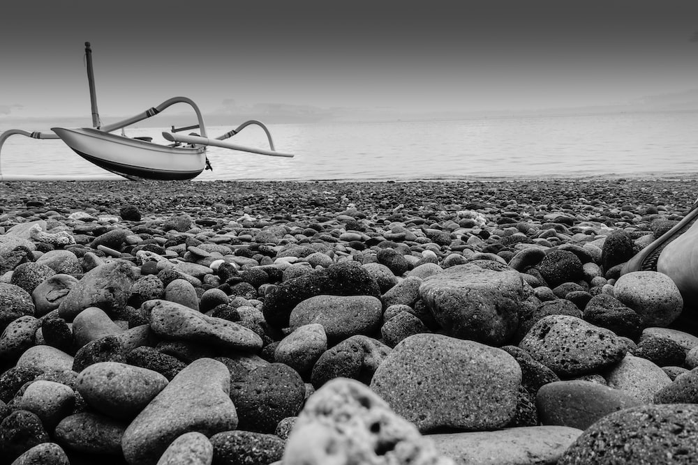 grayscale photo of white boat on beach