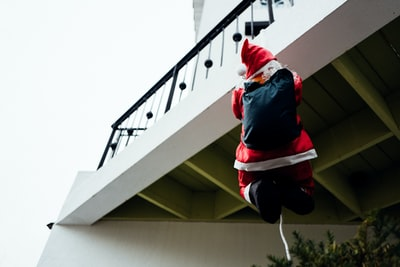 person in red jacket holding the white rope attached to black metal balcony fence santa teams background