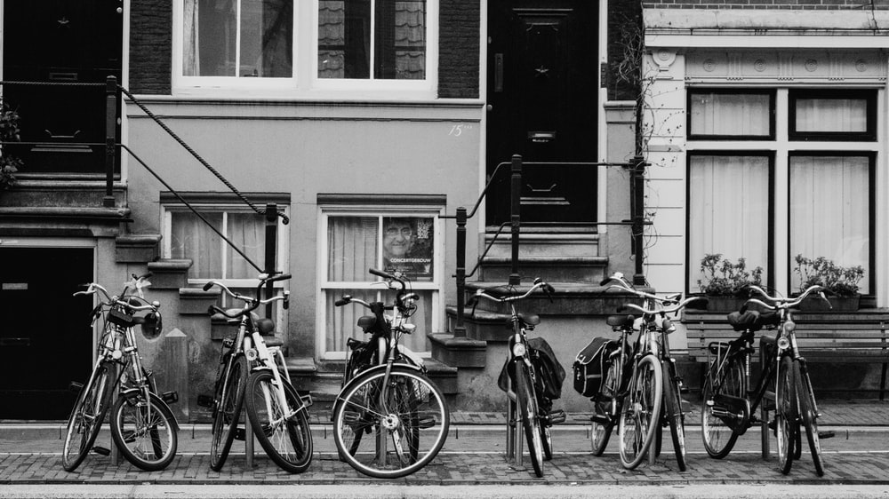 grayscale photo of bikes parked near house