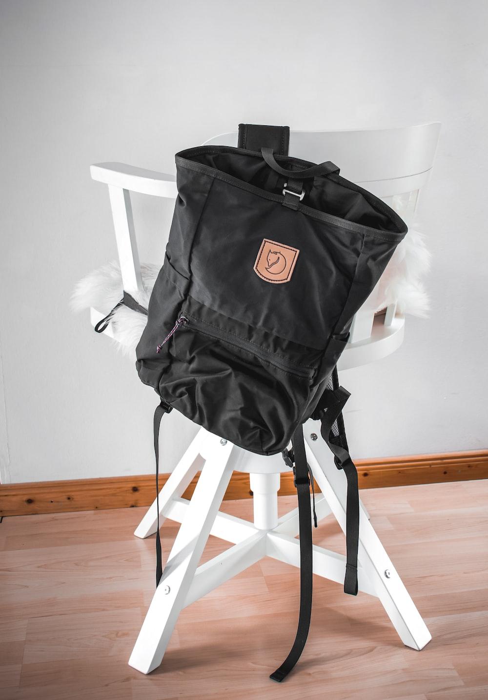 black bag on white wooden chair