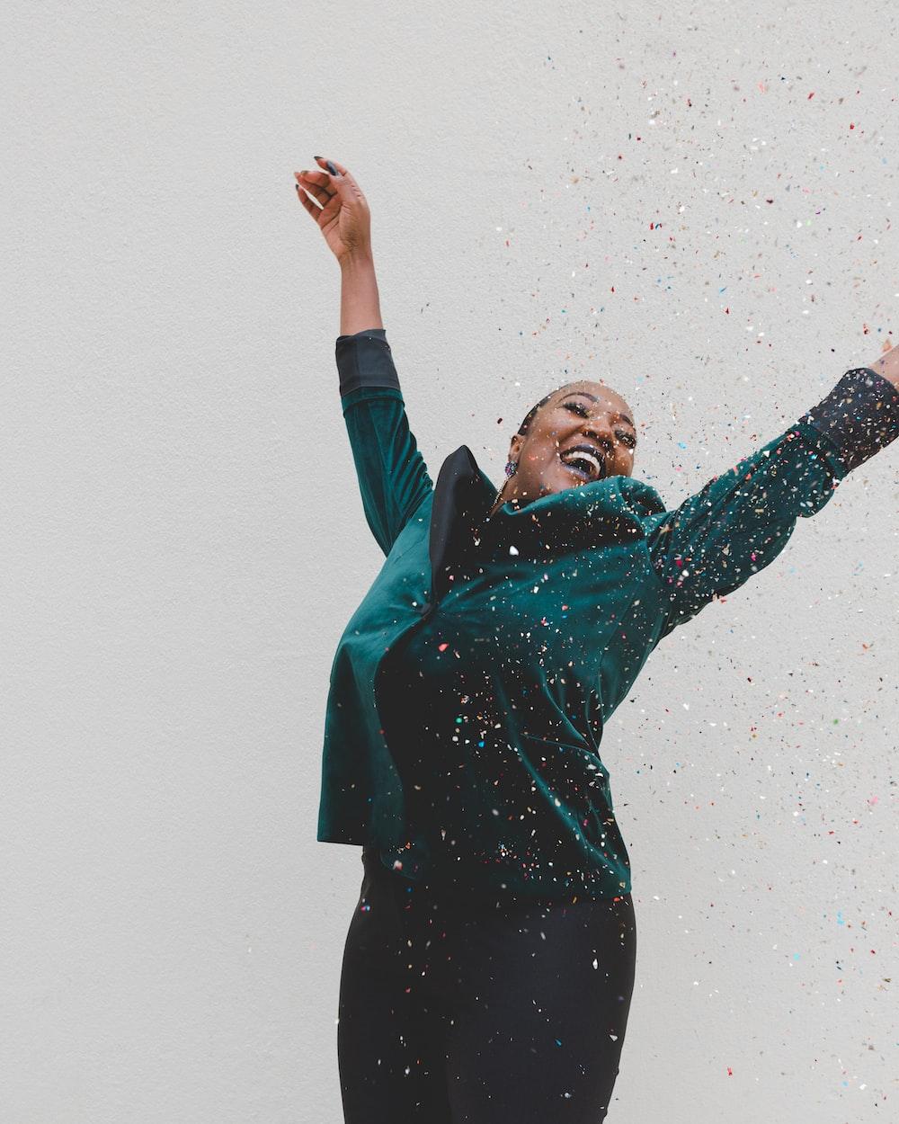 woman in green jacket raising her hands