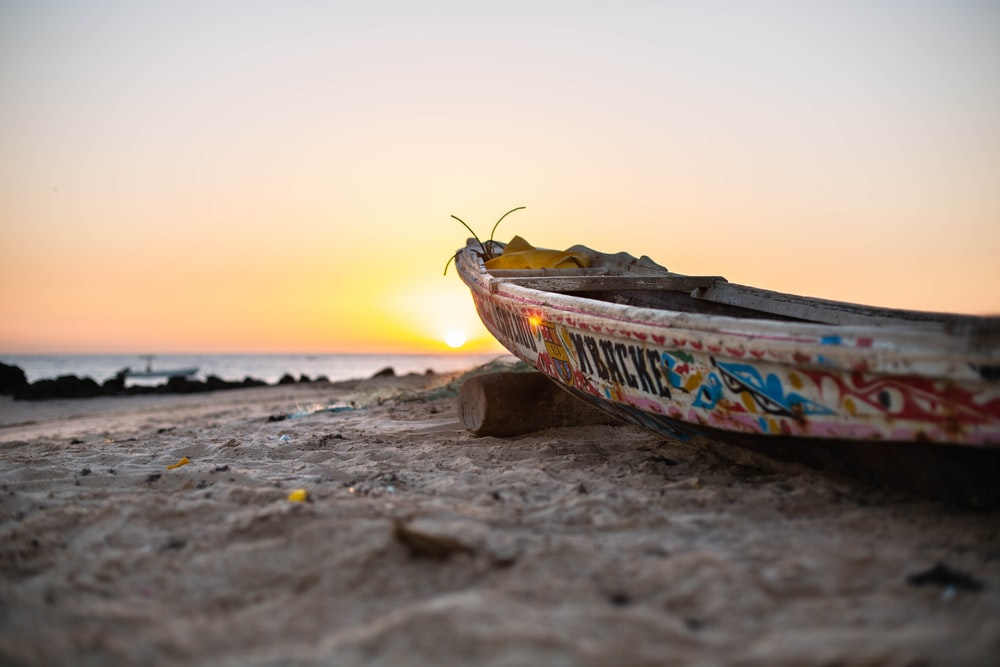 multicolored boat on brown sand
