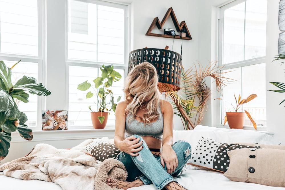 woman in gray sports bra sitting on bed near windows