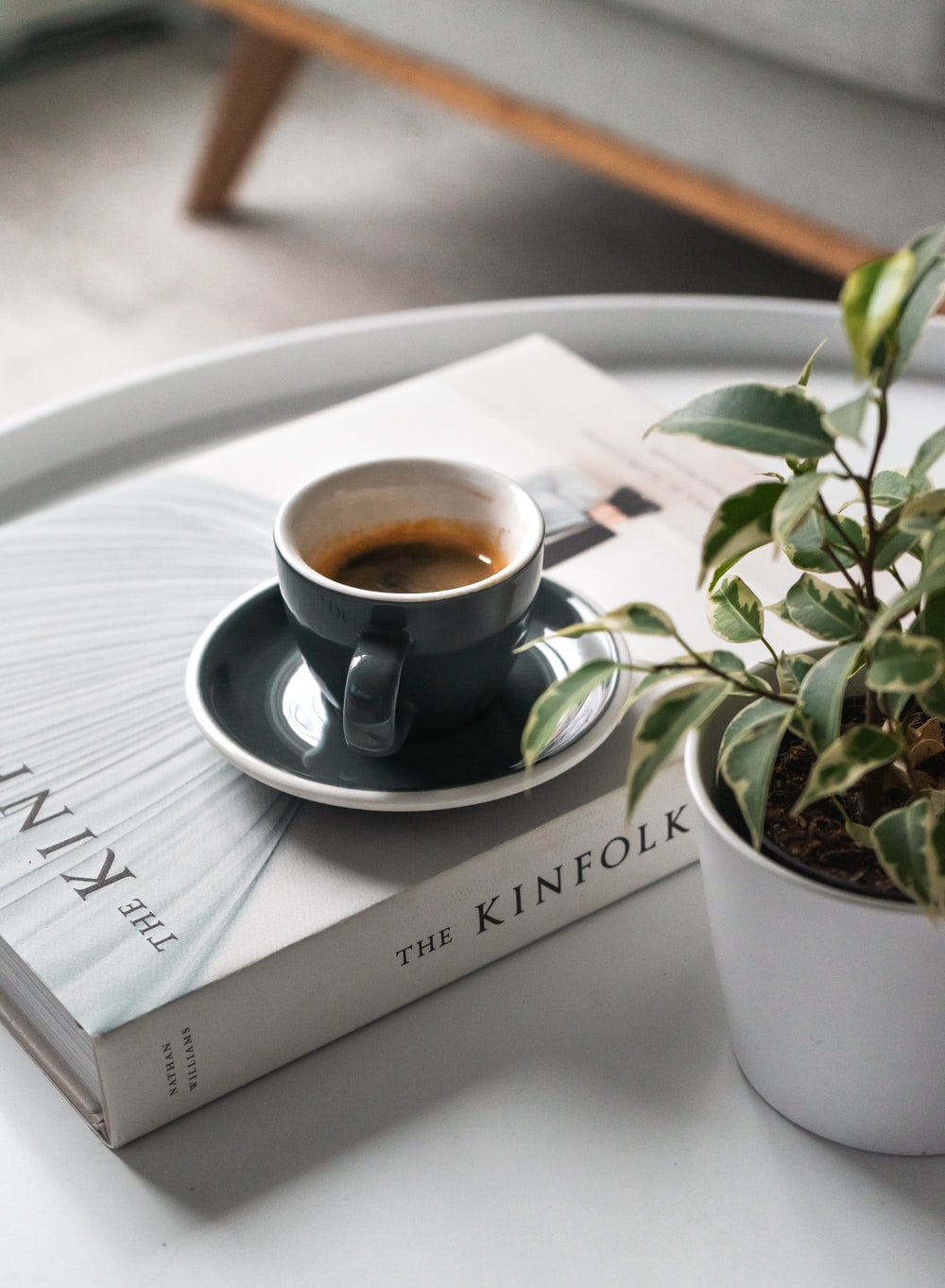 shallow focus photo of black ceramic mug and saucer on white book