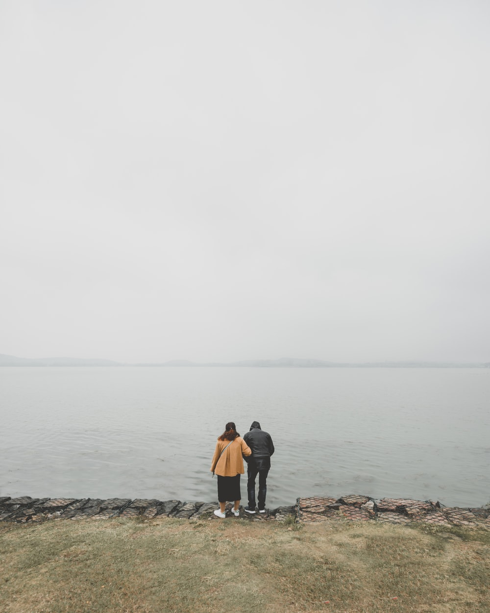 two person standing in front of body of water during daytime