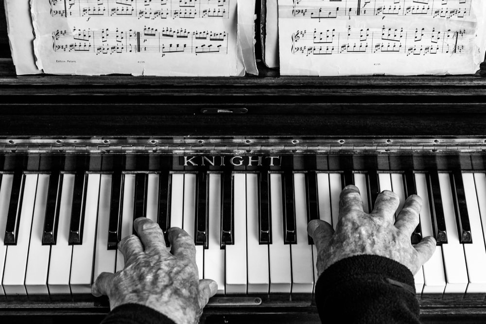 person playing piano in grayscale photo