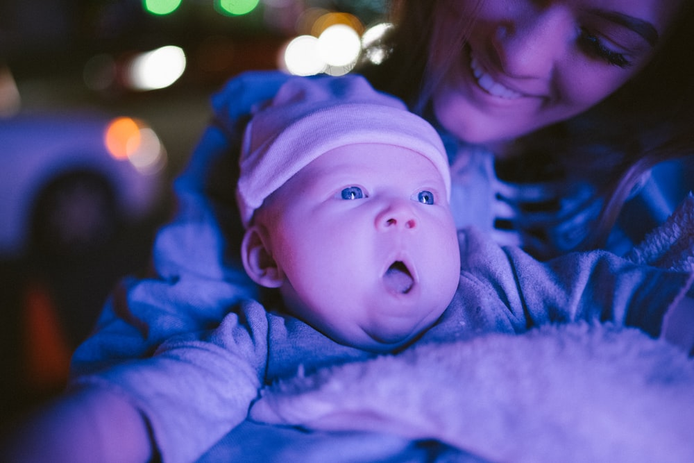 selective focus photography of woman holding baby