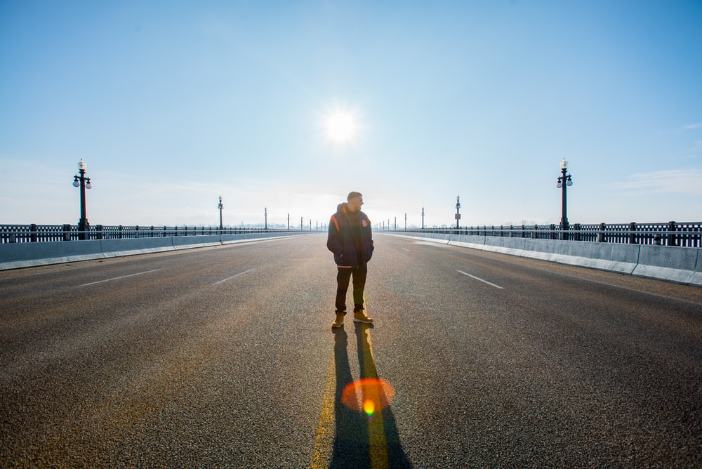 man standing on road