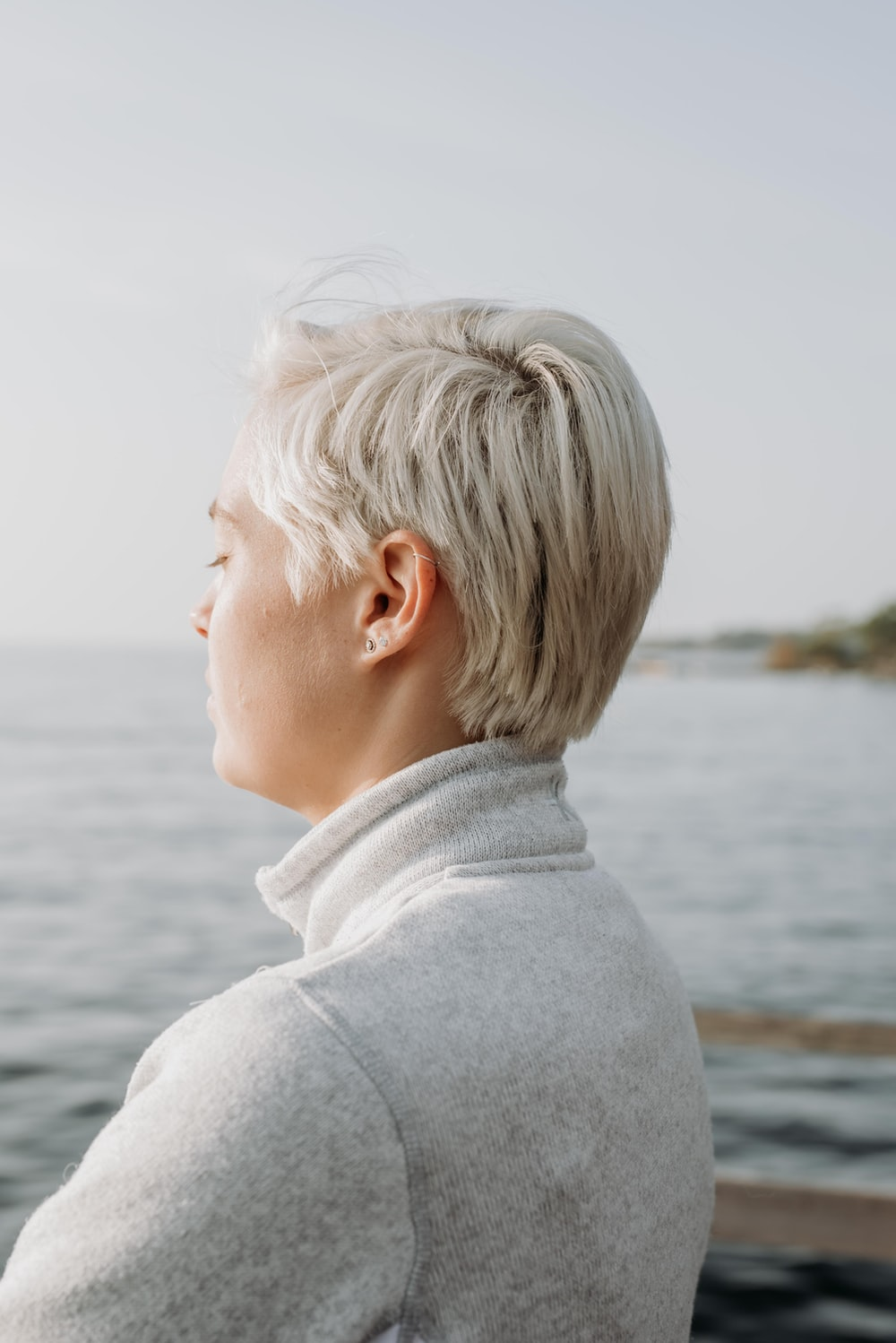 woman with blonde hair wearing gray sweater at dock