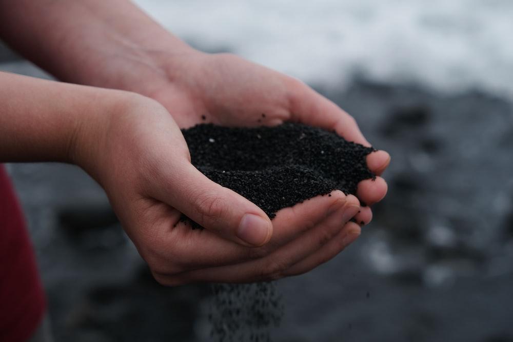 person holding black soil