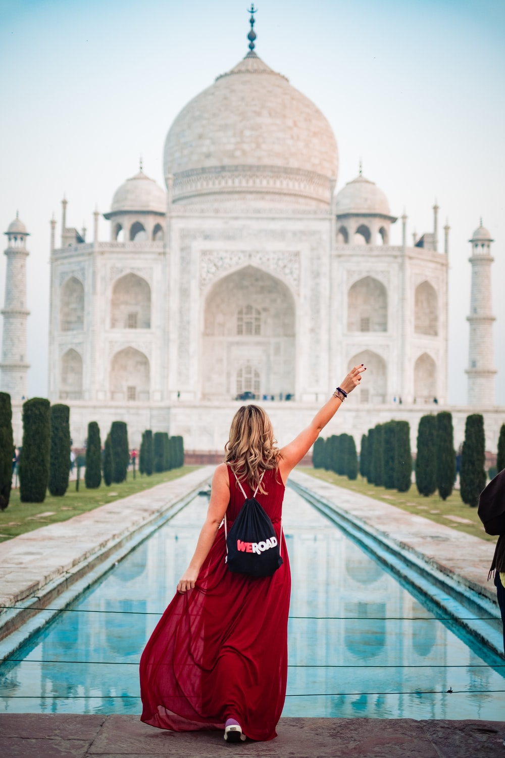 woman in red dress standing in front of Taj Mahal