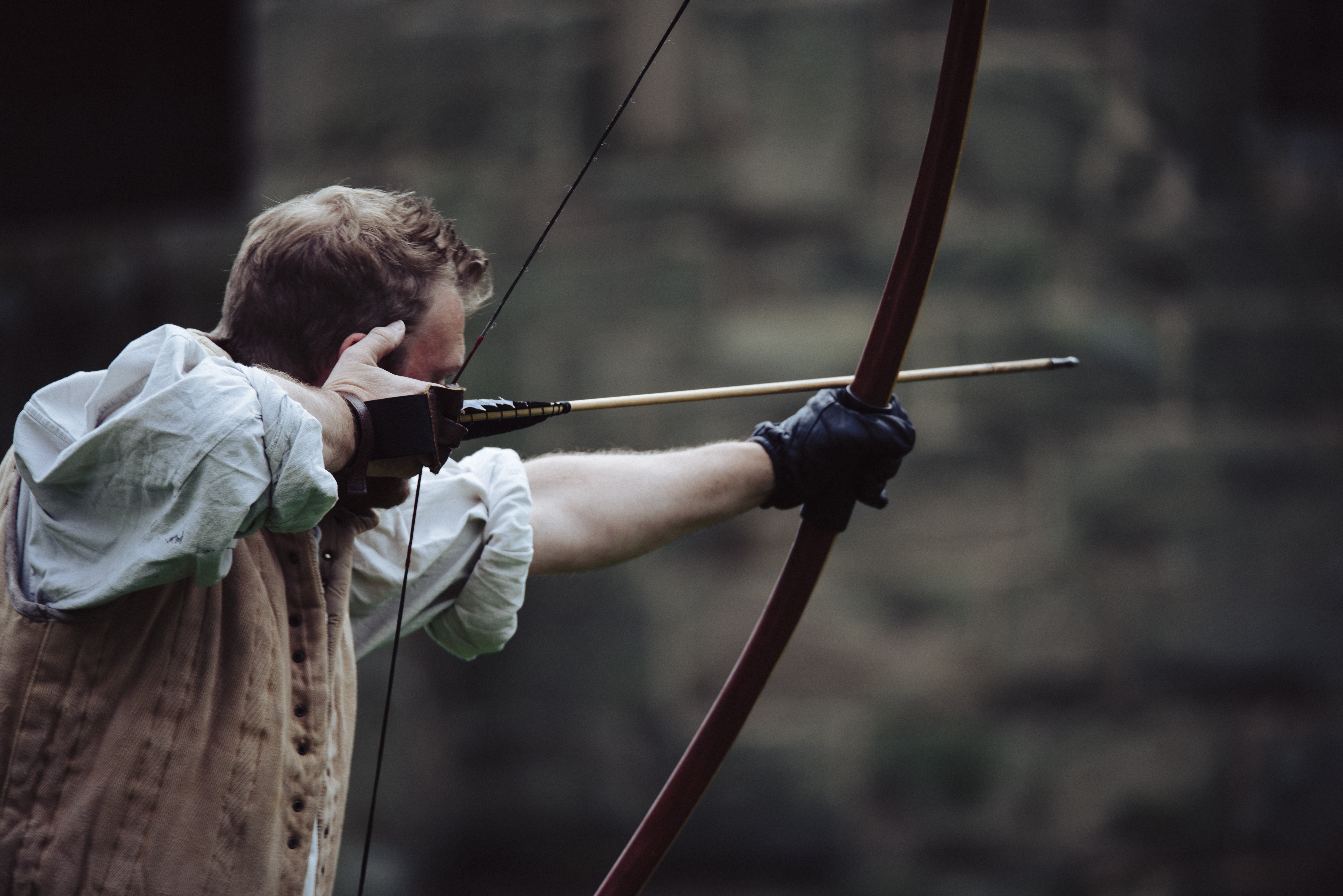 man using brown bow with arrow