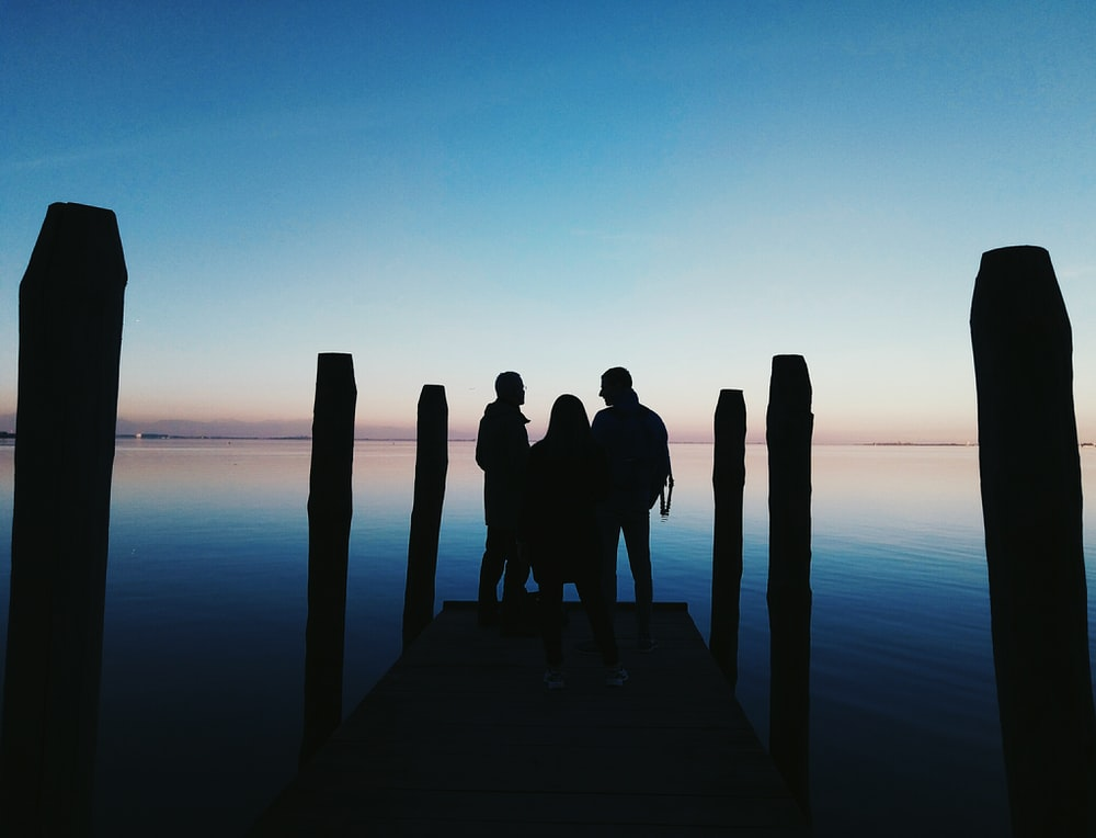 silhouette of three person on seadock