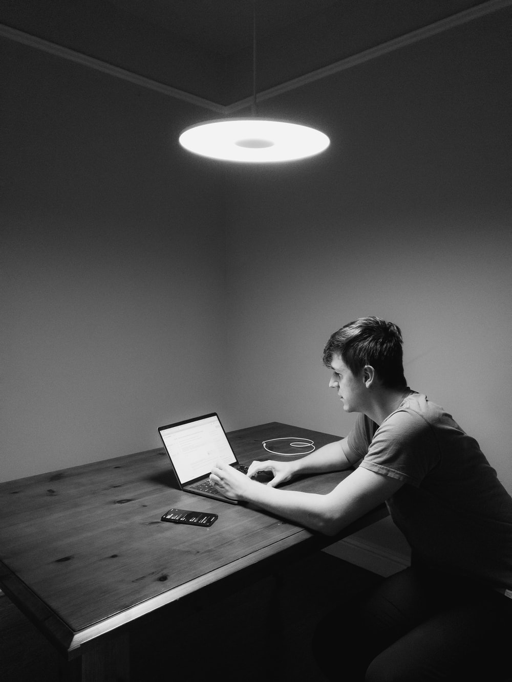 grayscale photography of man siting facing laptop computer