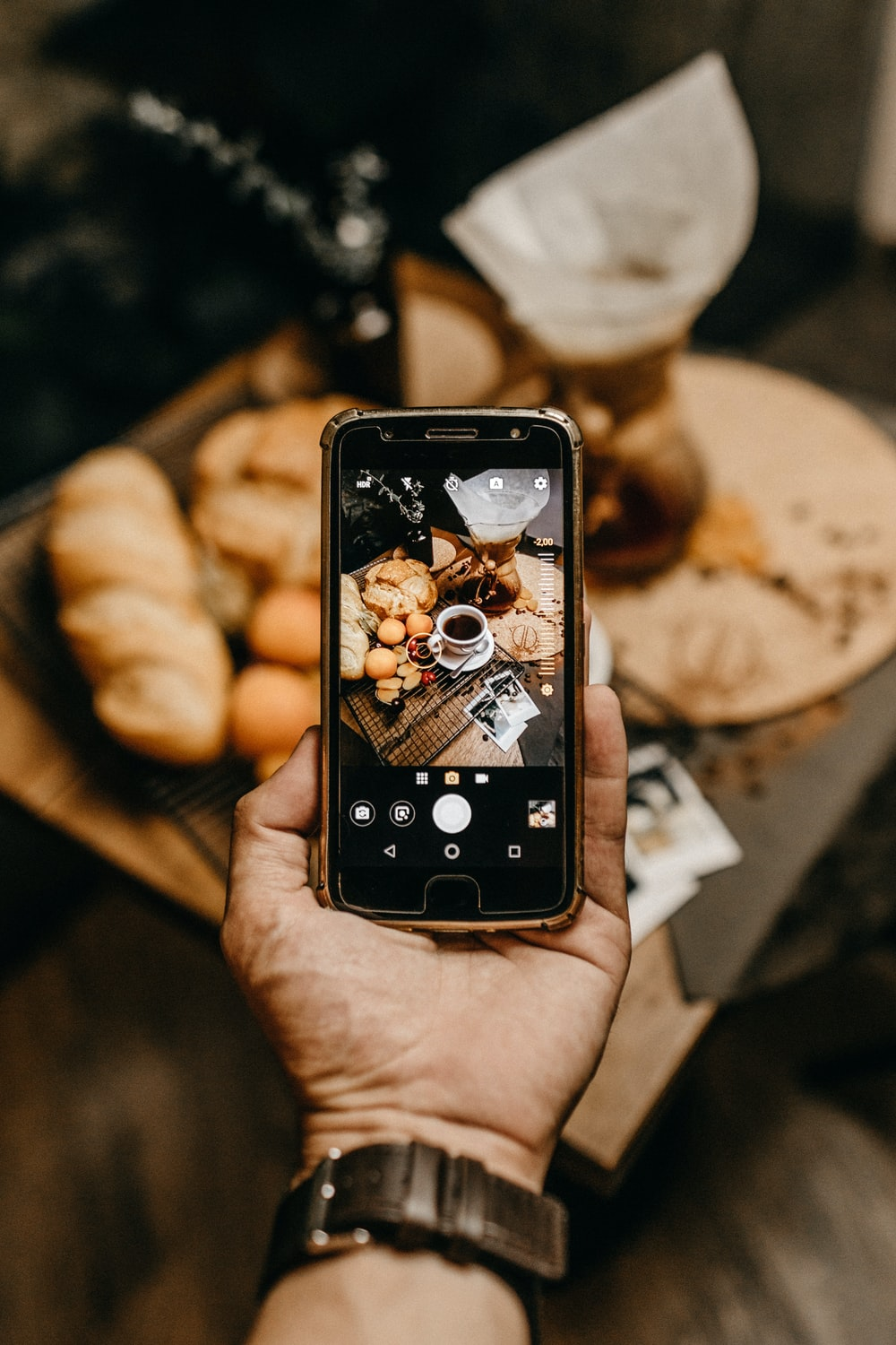 person capturing breads and coffee on smartphone