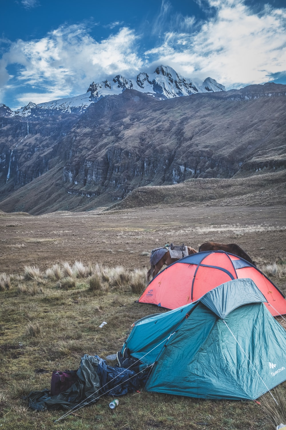 two blue and red camping tents on mountain