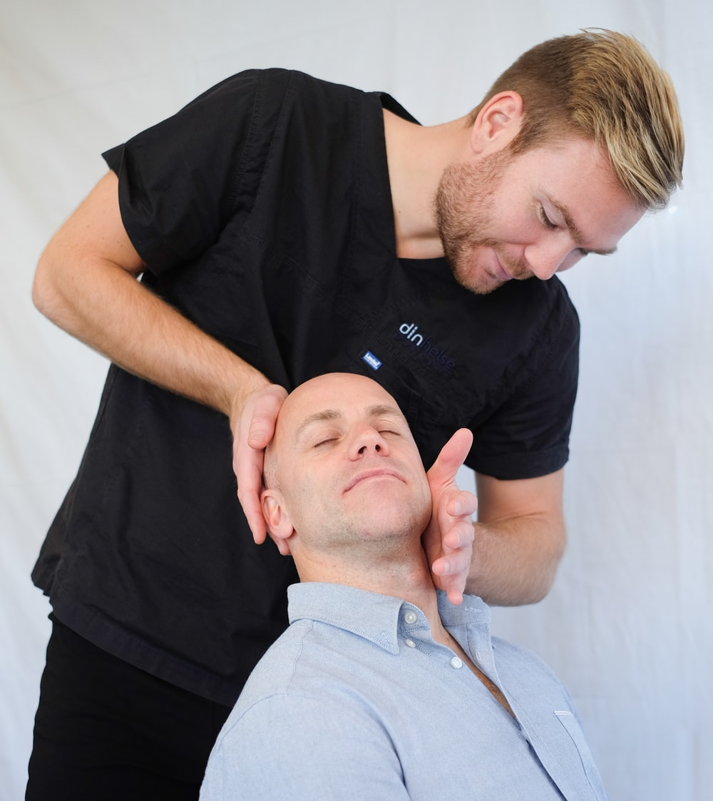 man in black medical scrub top massaging man's neck