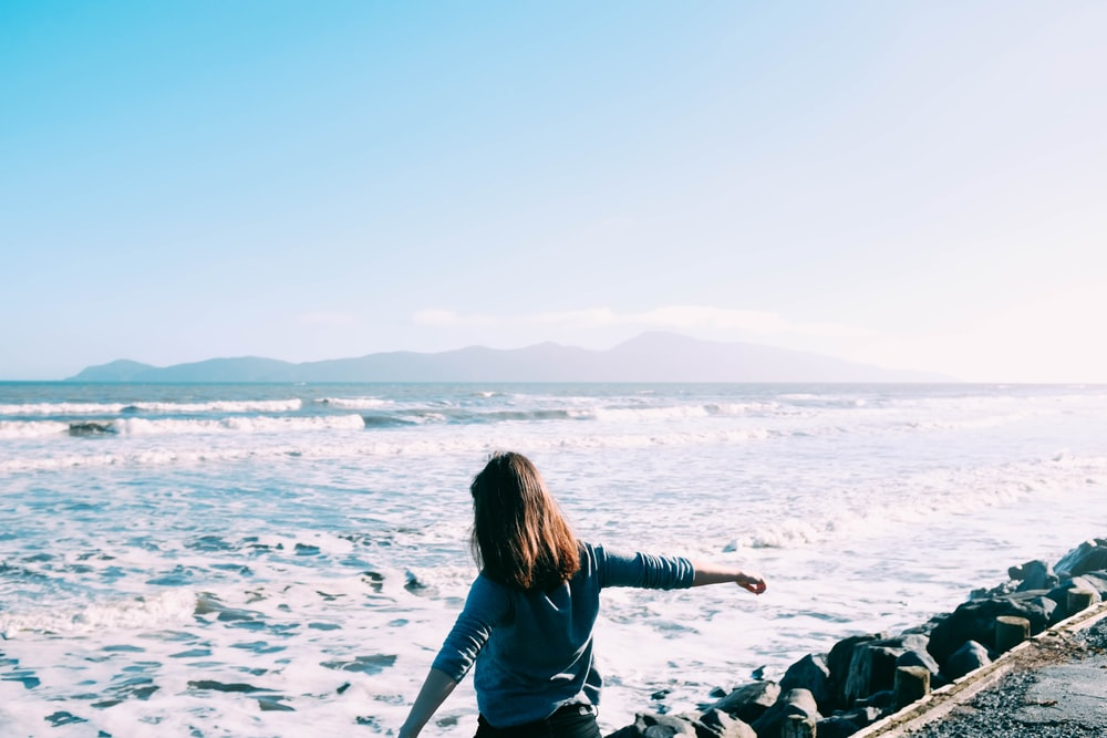woman standing in front of body of water during daytime