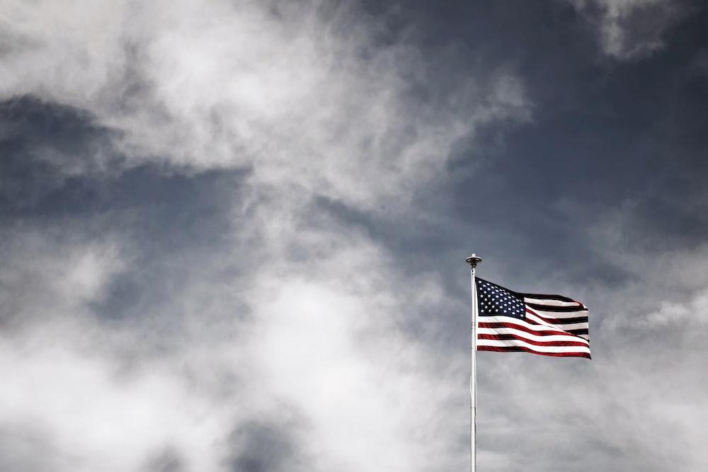 waving USA flag under grey sky