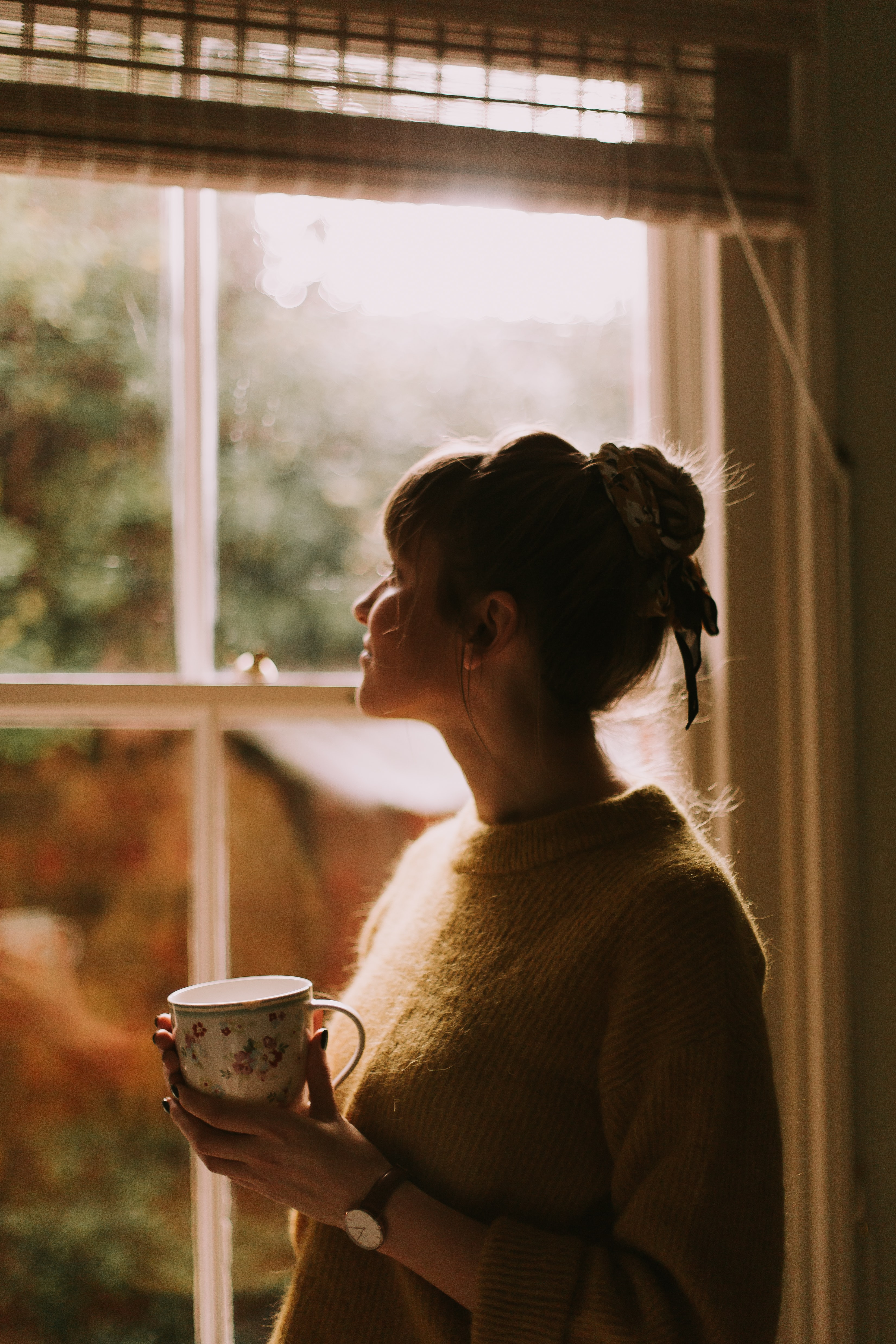 woman holding teacup while standing near window inside room during daytime