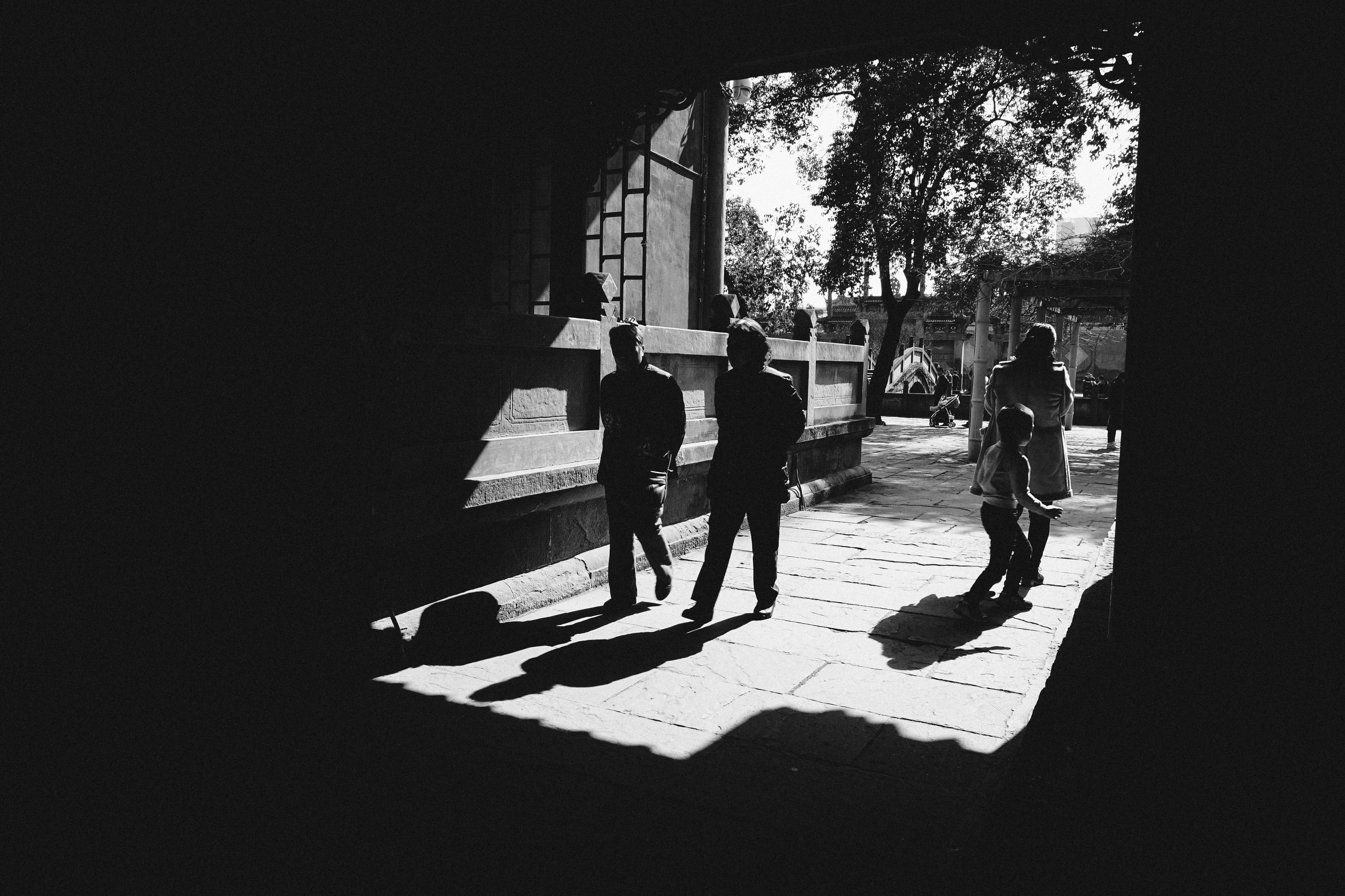 grayscale photography of four persons standing near building