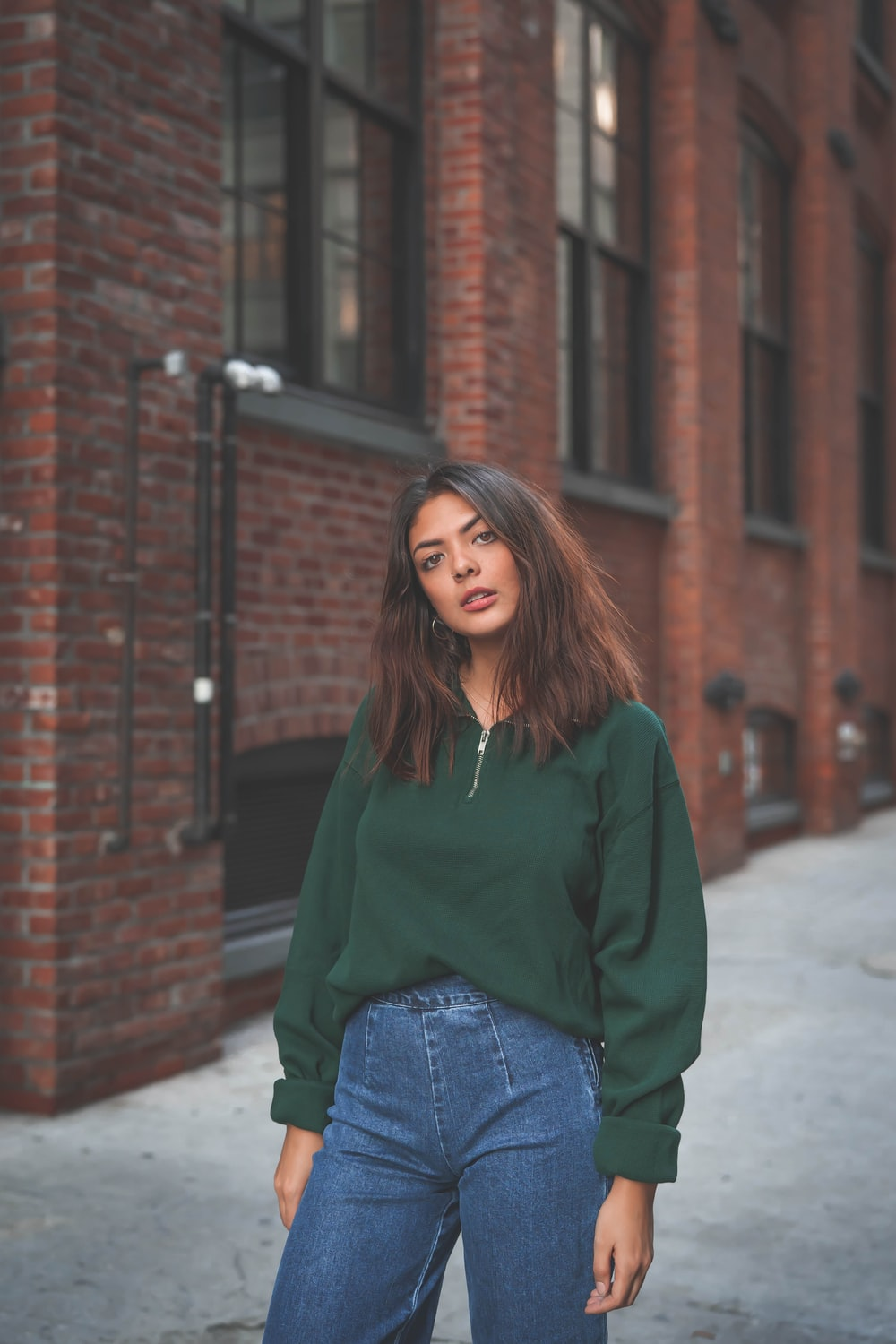 woman in green sweater and blue pants by buildingg