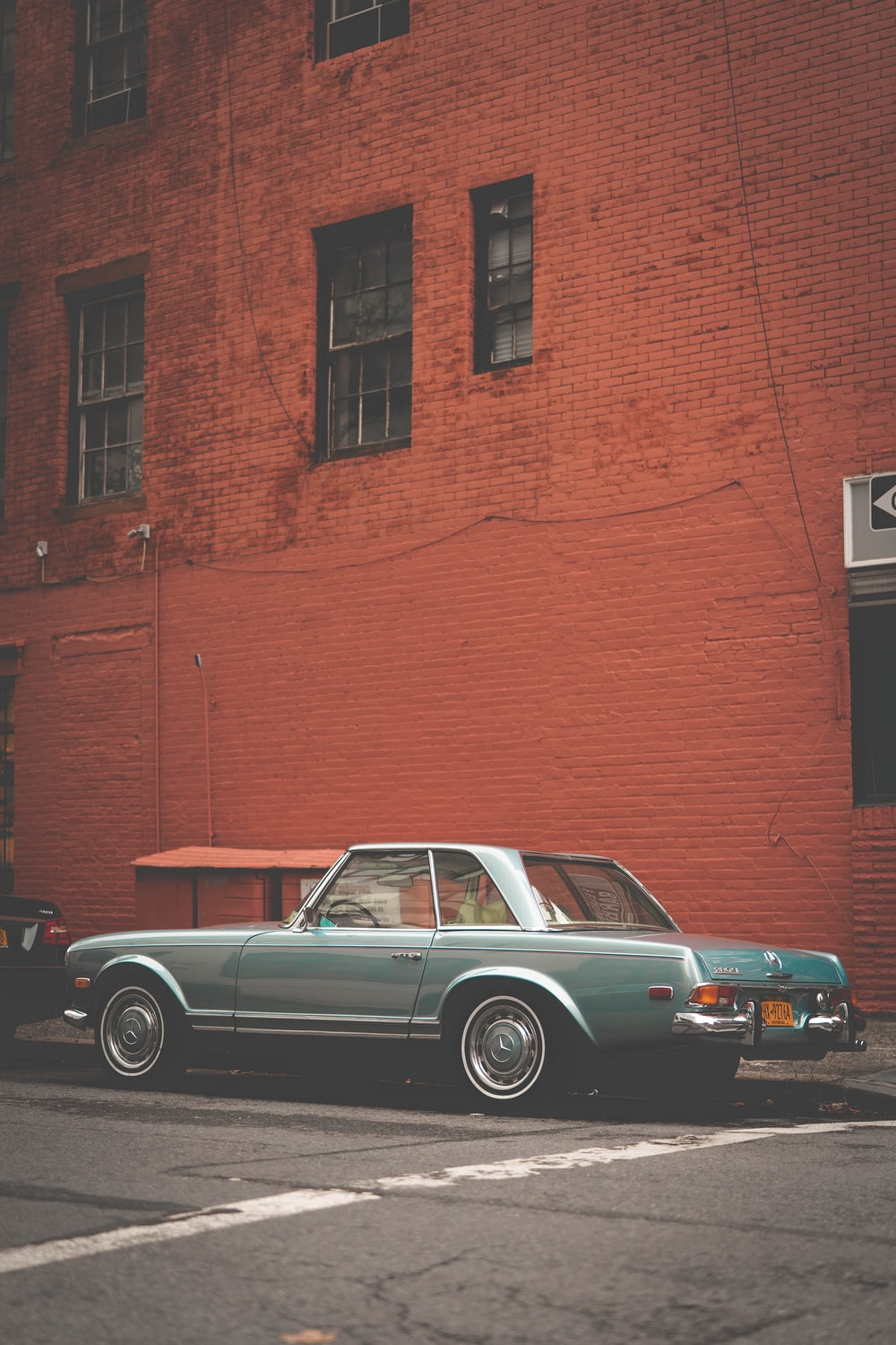 parked gray coupe beside brown concrete building
