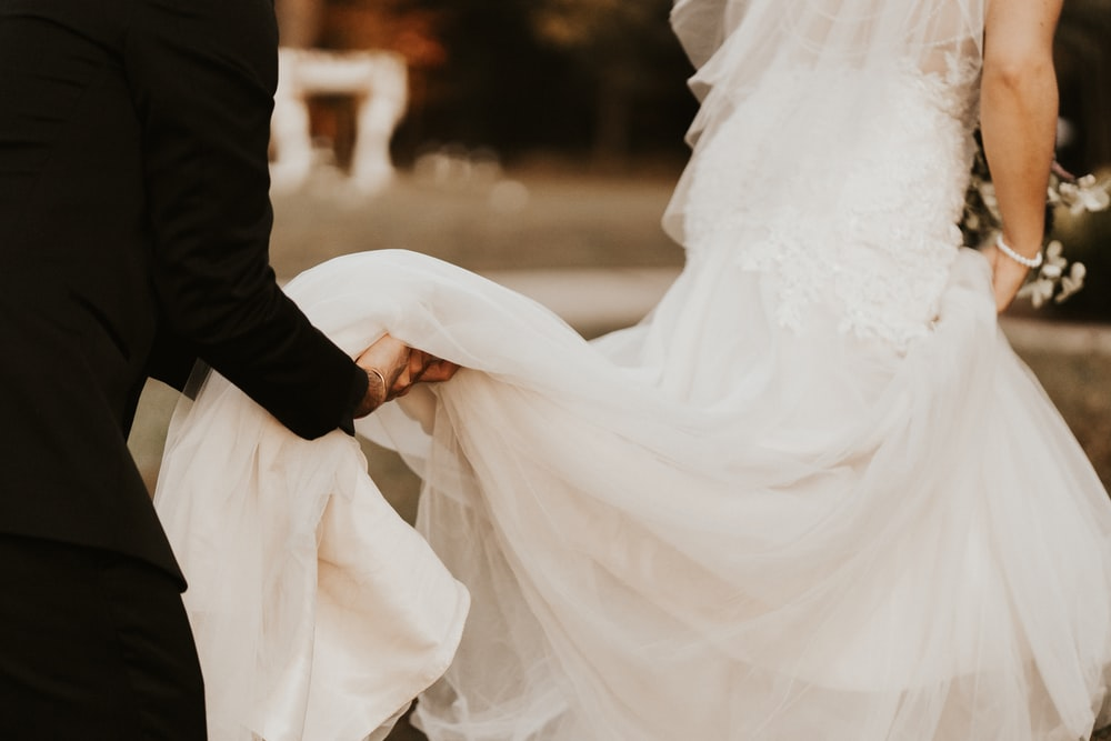 man helping bride with her wedding dress