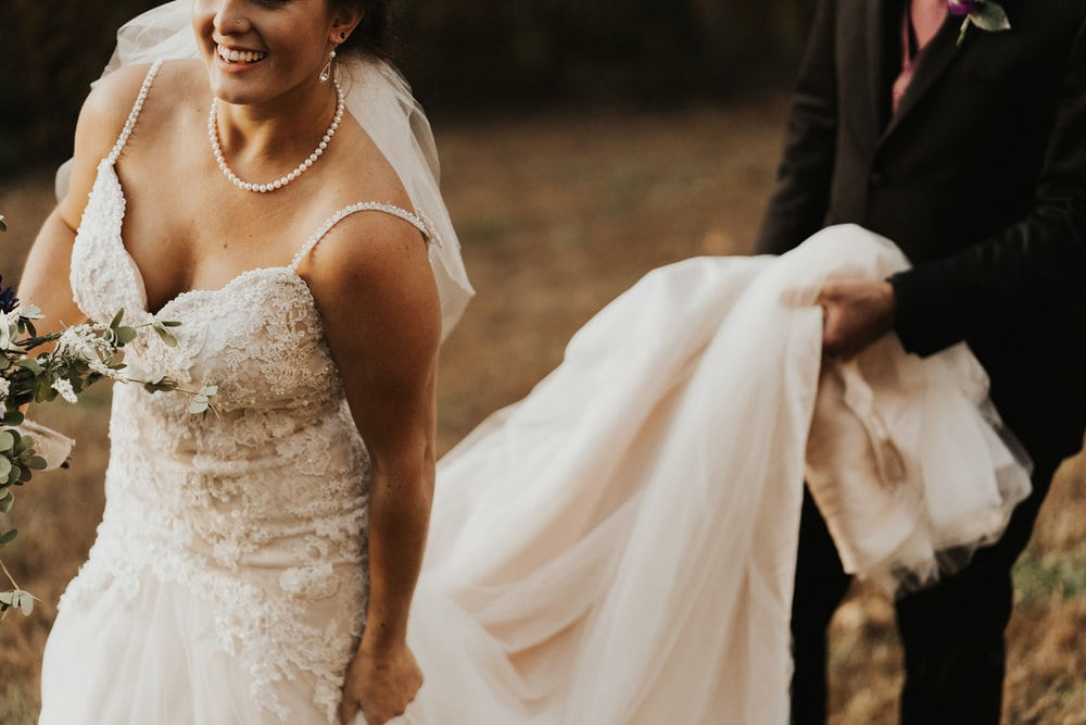 man holding women's white wedding gown