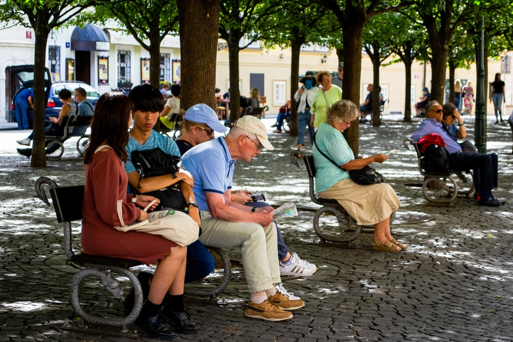 man in blue polo shirt sitting on bench beside man in blue cap