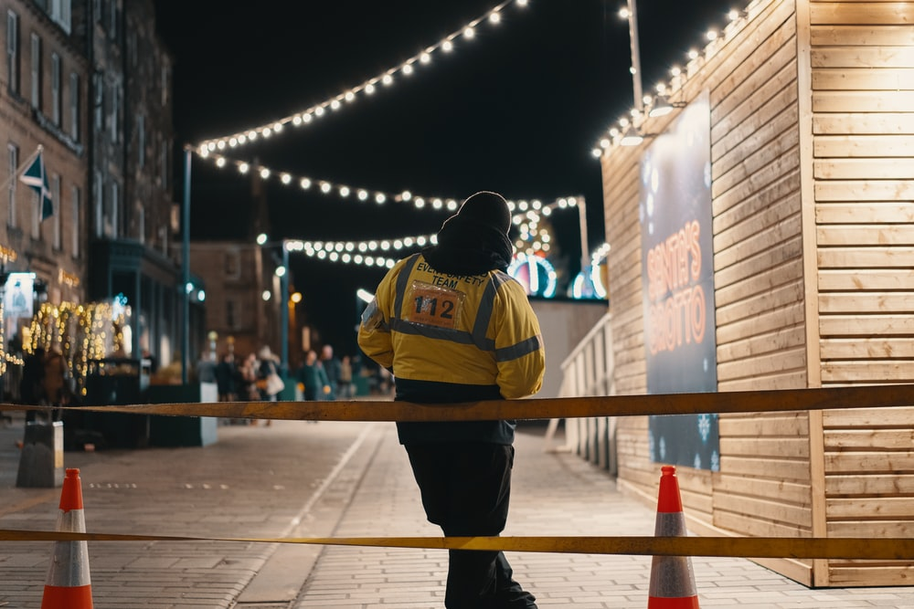 person in yellow jacket leaning on rail