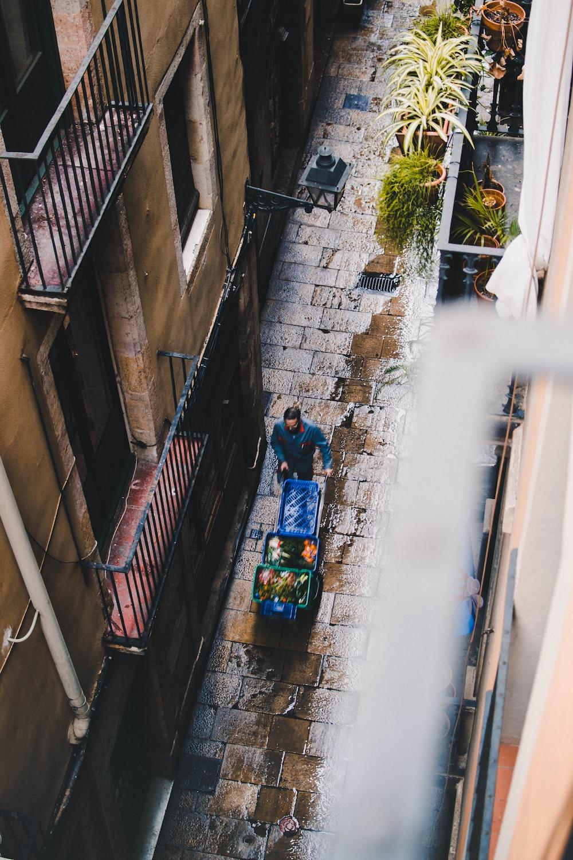 man blue pushing cart during daytime