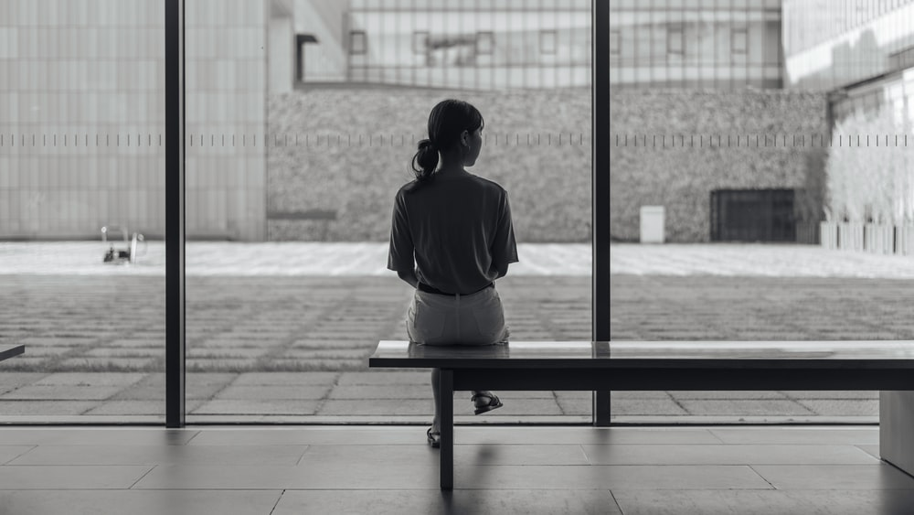 woman sitting on bench in greyscale photography
