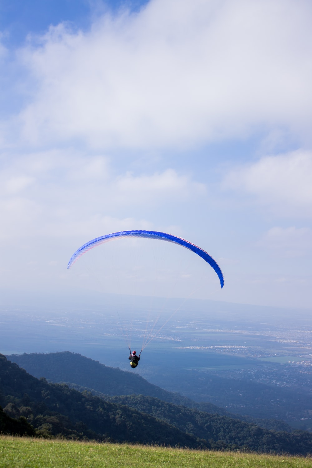 man with parachute near mountain and village