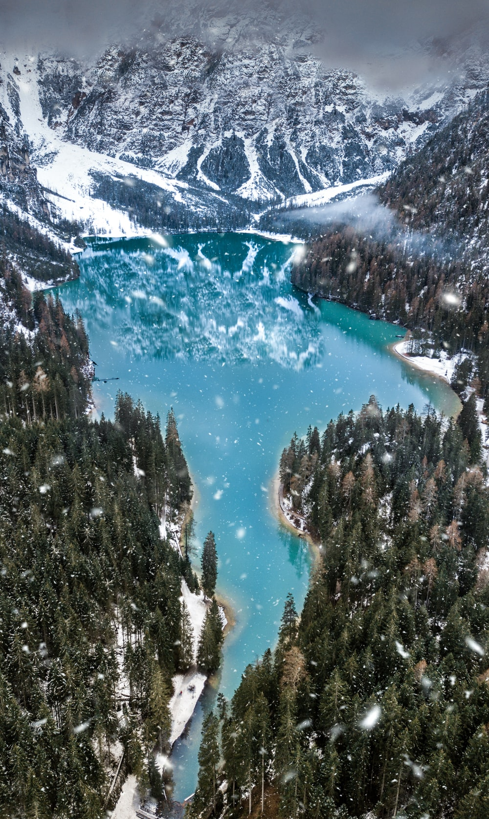 aerial photo of snow covered mountain near body of water