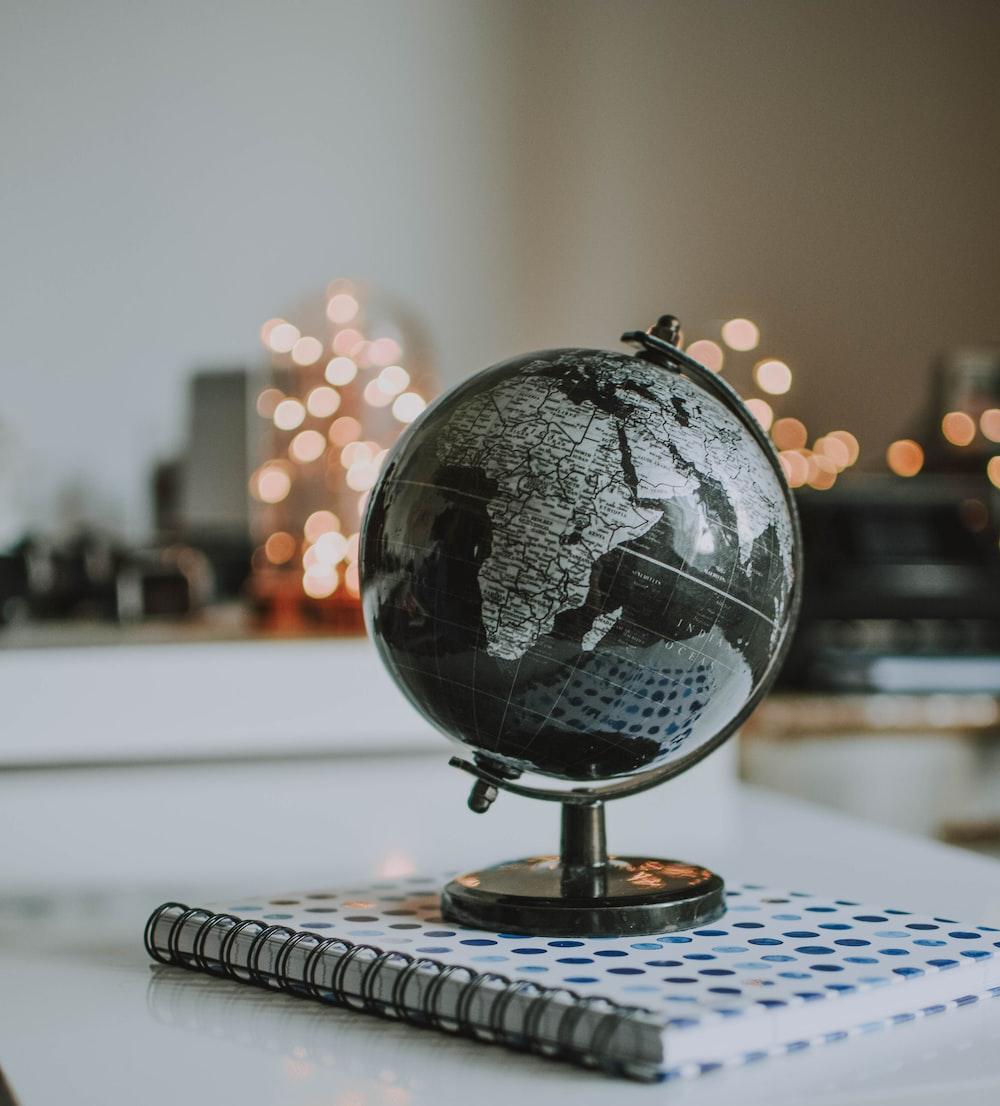 black and gray desk globe on notebook