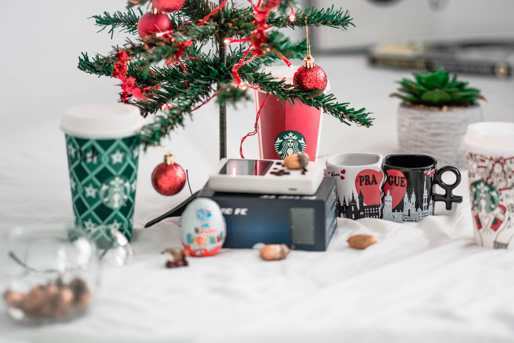 two ceramic mugs beside two cups and christmas tree