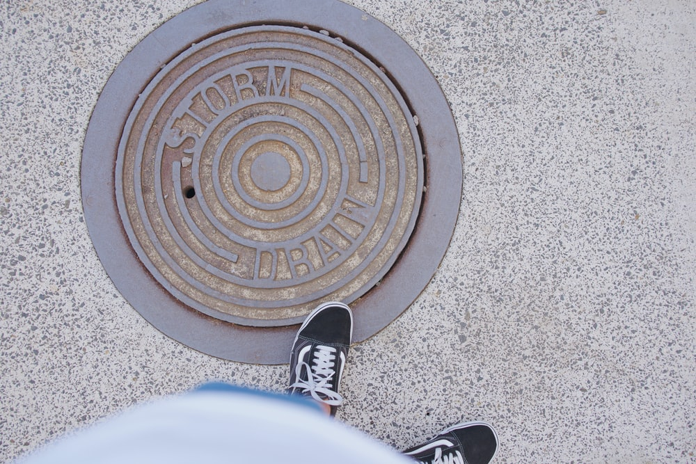 person standing next to manhole