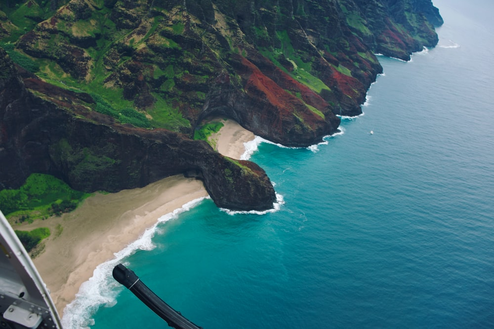 aerial photography of shore, cove and mountain