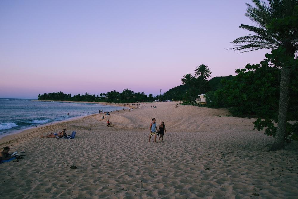 woman and man walking around beach