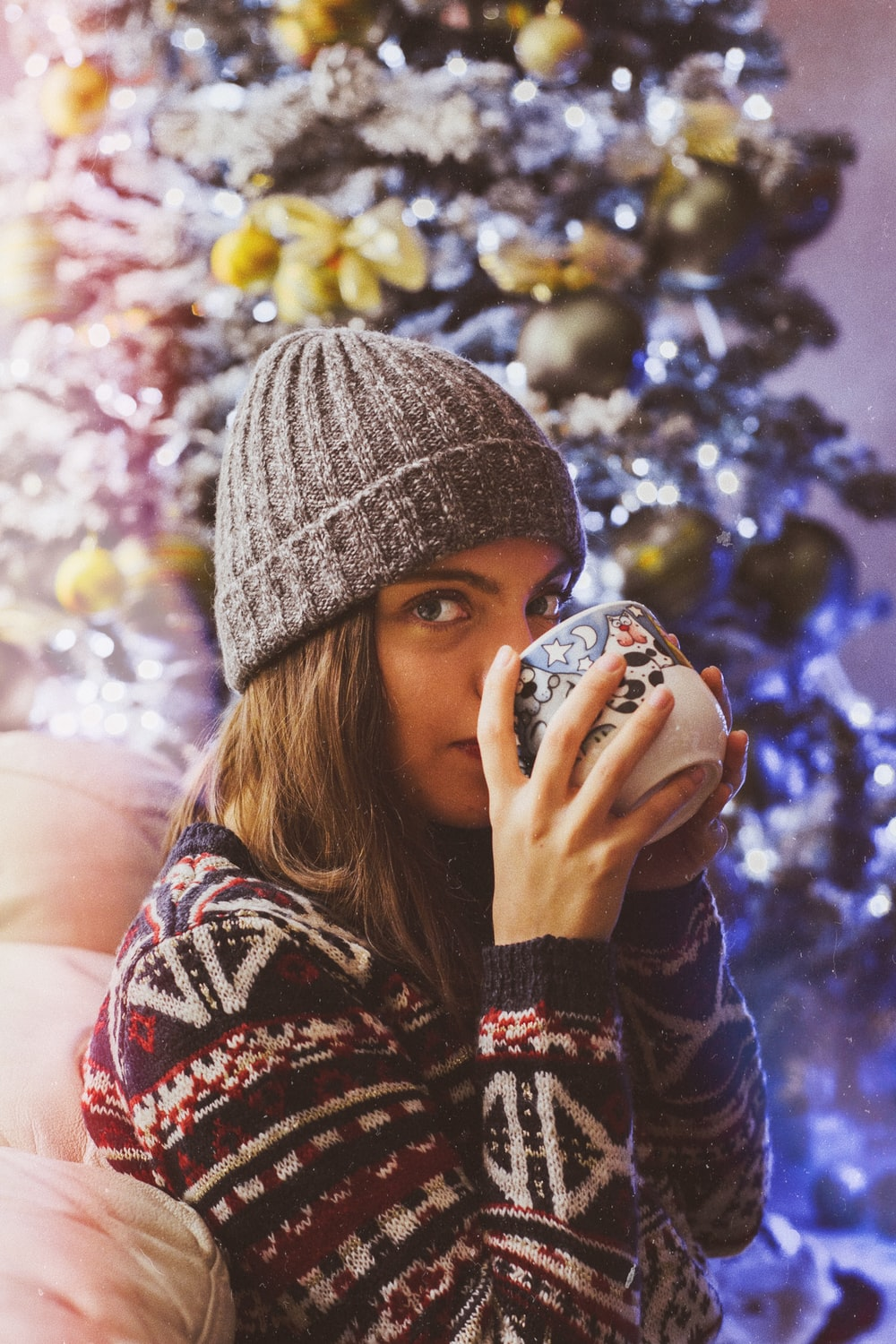 woman drinking from cup near Christmas tree