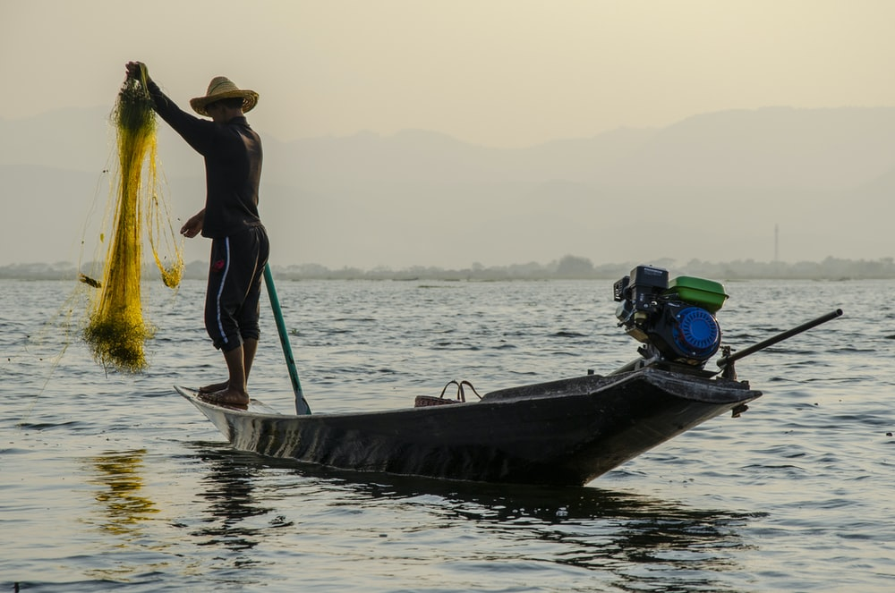 man holding fish net standing on boat