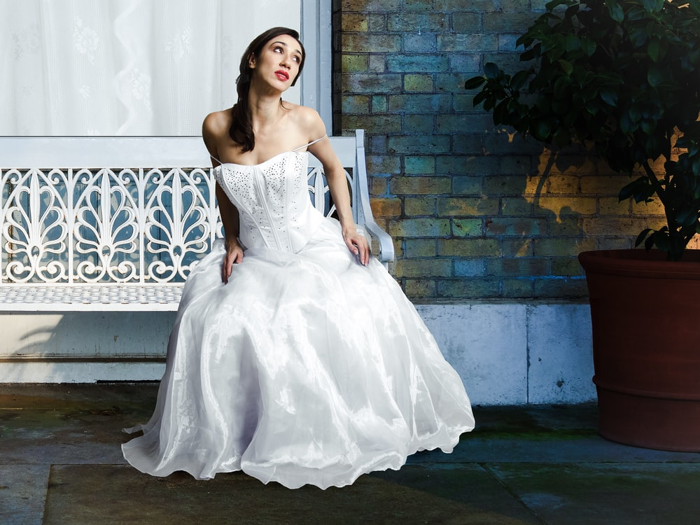 woman wearing wedding dress while sitting on white bench
