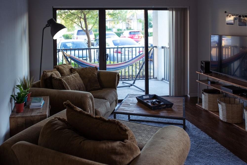 two brown sofa chairs beside glass window