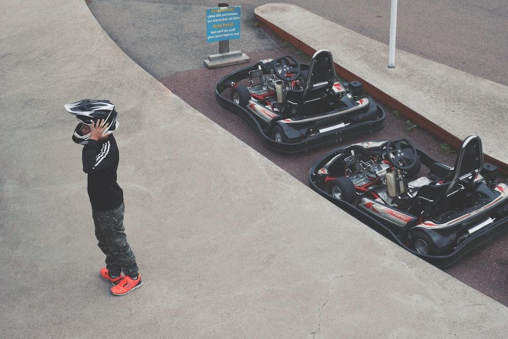 person wearing helmet standing beside two go-karts