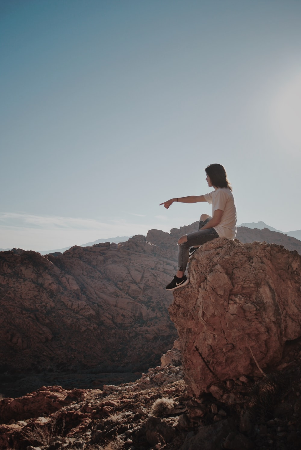 man sitting on rock under blue sky